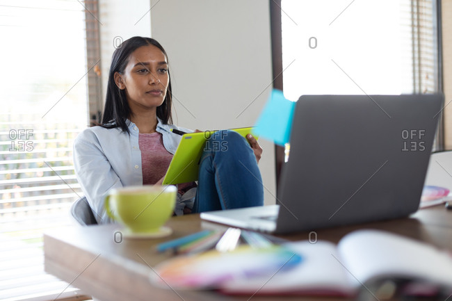 Mixed race woman sitting at table holding clipboard working at home