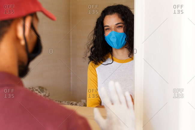 Mixed race woman wearing a face mask greeting delivery man at door