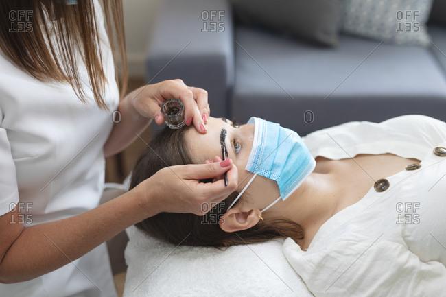 Caucasian woman wearing face mask lying down having eyebrows dyed