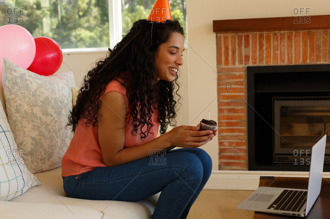 Mixed race woman celebrating birthday having video chat on laptop