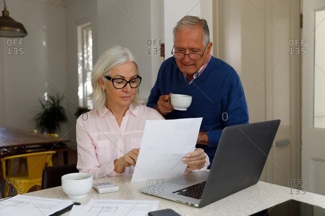 Senior caucasian couple with laptop calculating finances at home