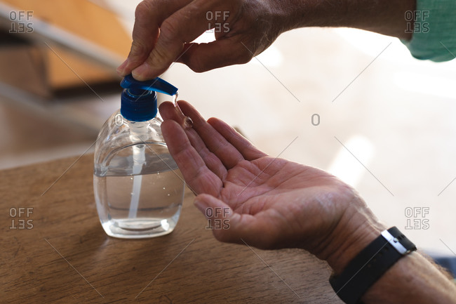 Hands of senior caucasian man cleaning hands with sanitizing gel