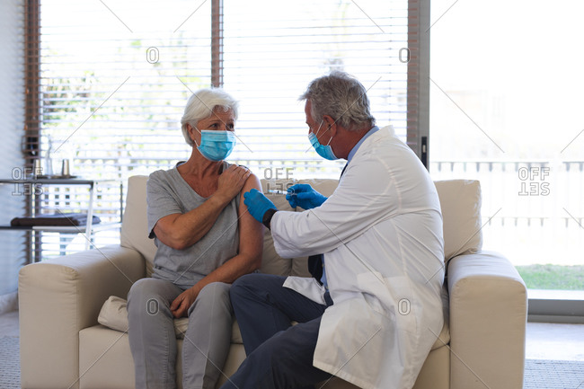 Caucasian male doctor giving covid19 vaccination to senior woman