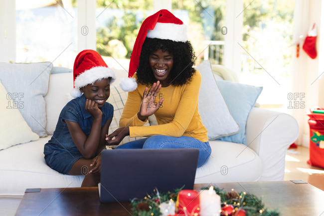African american mother and daughter having video chat on laptop