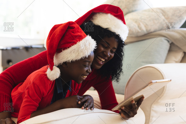 African american mother and daughter having video chat on tablet