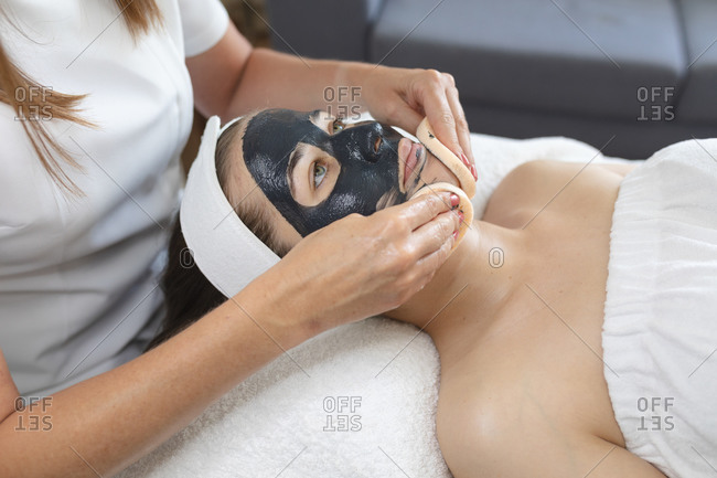 Caucasian woman lying back while beautician applies a face mask