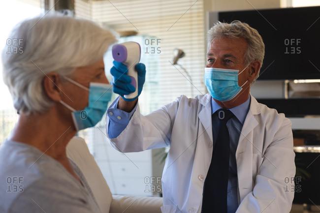 Senior caucasian male doctor taking temperature of senior woman