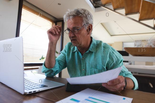 Senior caucasian man sitting at table using laptop paying bills