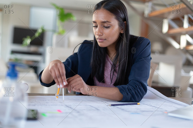 Mixed race woman sitting at table using compass working at home