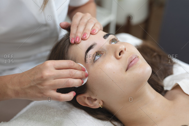 Caucasian woman lying back while beautician wipes her eyebrows