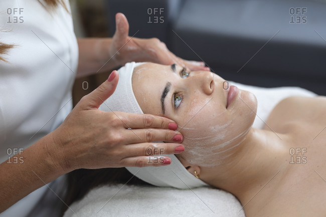 Caucasian woman lying back while beautician gives her a facial