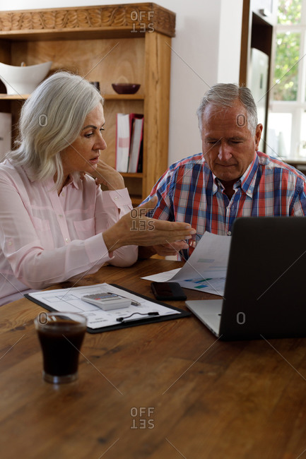 Stressed senior caucasian couple calculating finances at home