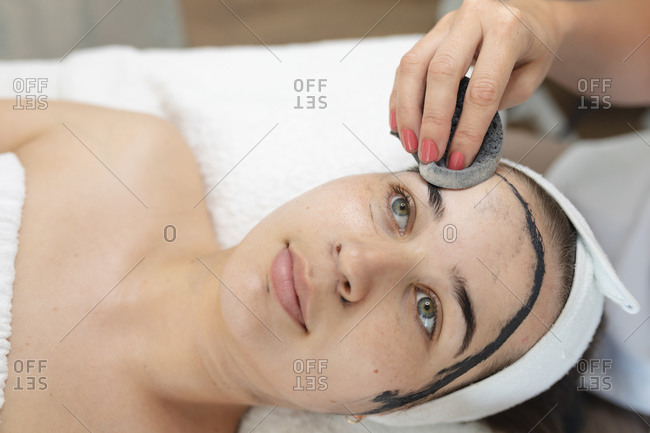 Caucasian woman lying back while beautician removes face mask