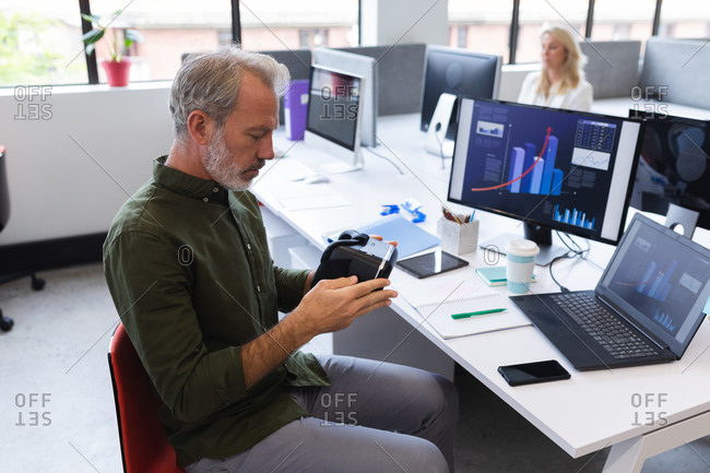 Caucasian man working in creative office, holding vr headset