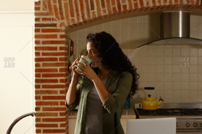 Mixed race woman drinking cup of coffee standing in kitchen