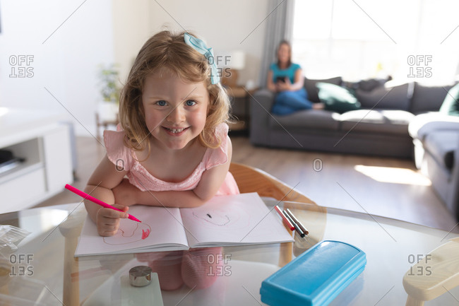 Smiling caucasian girl in living room, drawing in notebook