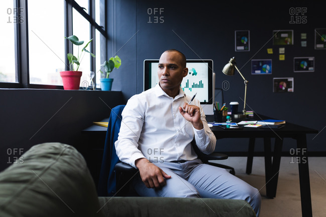 Mixed race businessman sitting by desk in office, thinking