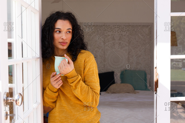 Mixed race woman standing in doors drinking cup of coffee