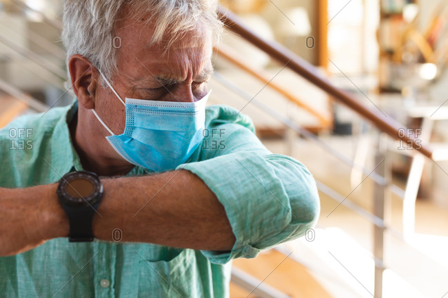 Senior caucasian man wearing face mask coughing into arm
