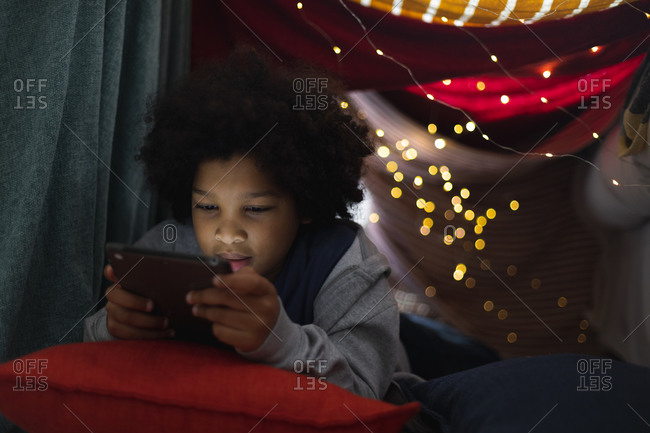 Mixed race girl lying in couch fort using digital tablet