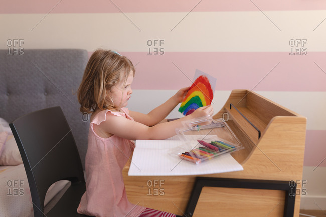 Caucasian girl holding drawing, sitting at desk at home