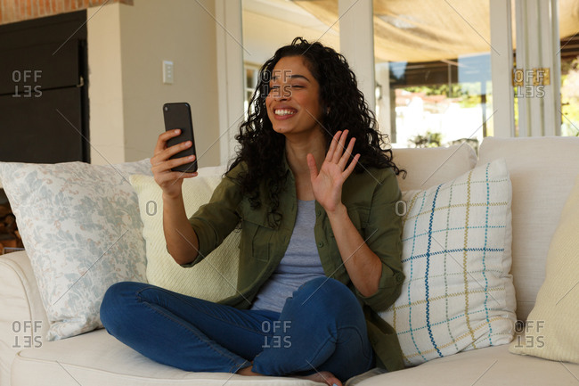 Mixed race woman having video chat on smartphone waving