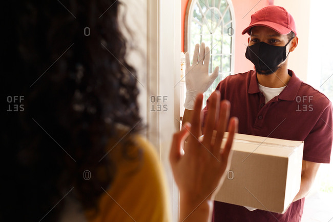 Mixed race woman wearing face mask receiving a package