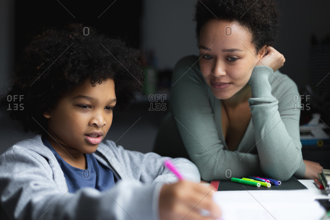 Mixed race woman watching daughter drawing in notebook