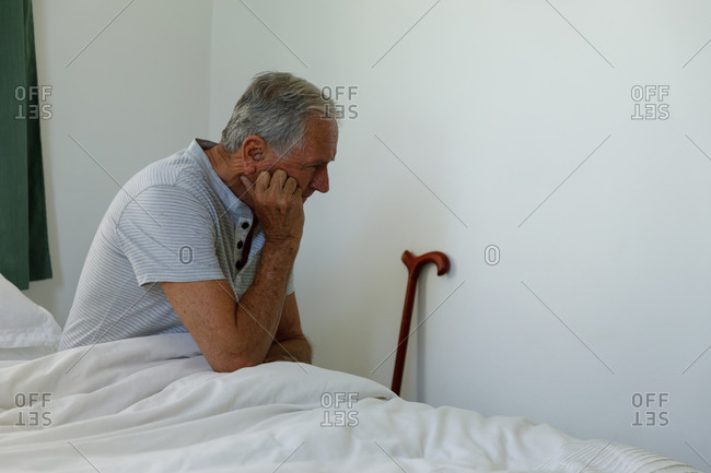 Stressed senior caucasian man sitting on bed at home