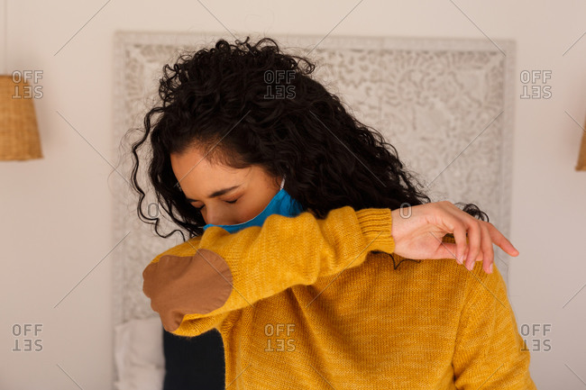 Mixed race woman wearing face mask coughing into arm