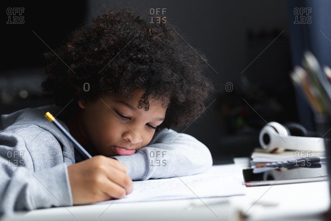Mixed race girl lying on a desk drawing in notebook