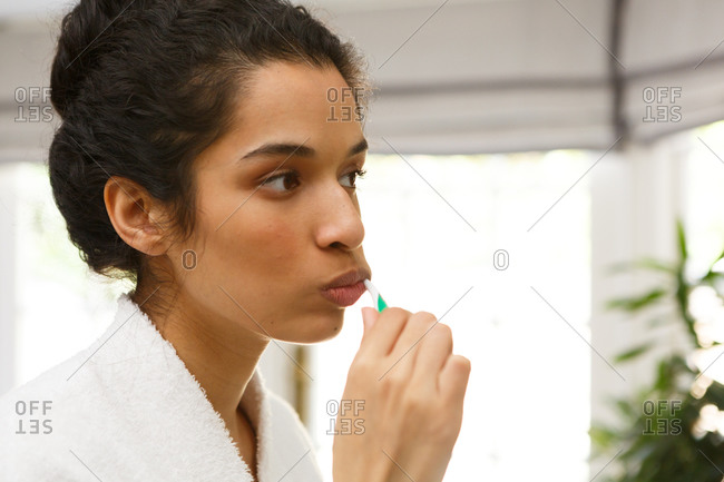Mixed race woman brushing her teeth in bathroom
