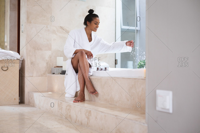 Mixed race woman sitting by a bathtub at home