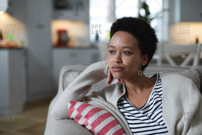 Mixed race woman sitting on couch looking sad