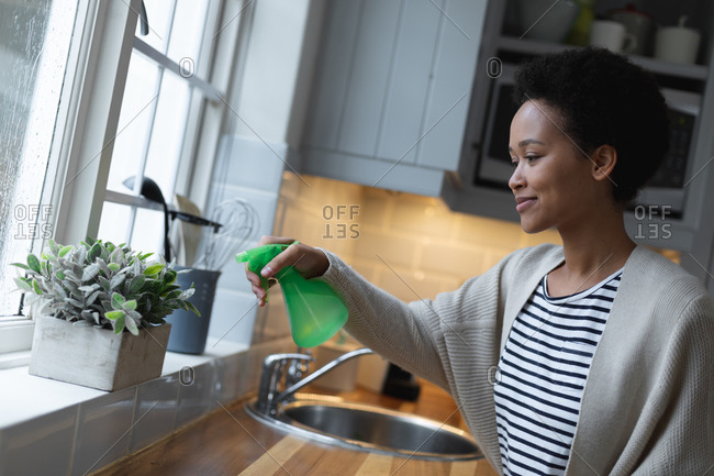 Mixed race woman watering plants in kitchen