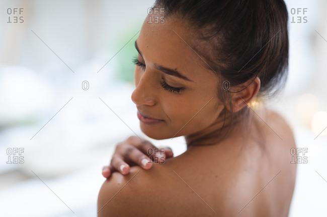 Mixed race woman lying a bathtub at home