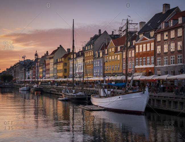 September 21, 2020: Denmark- Copenhagen- Boats moored along Nyhavn promenade at dusk with row of historical townhouses in background