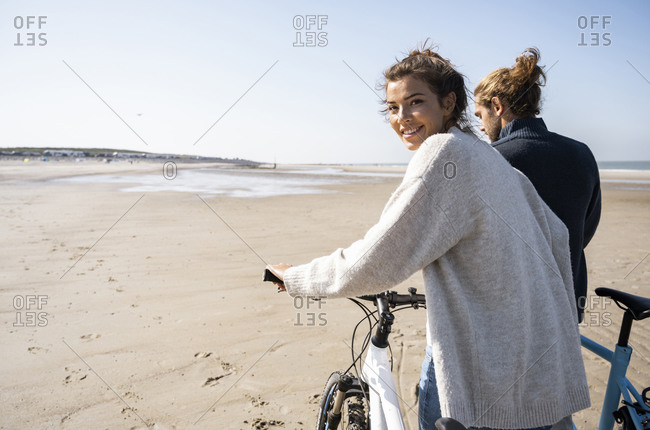 Smiling beautiful woman walking with bicycle by boyfriend while looking over shoulder at beach against clear sky on sunny day
