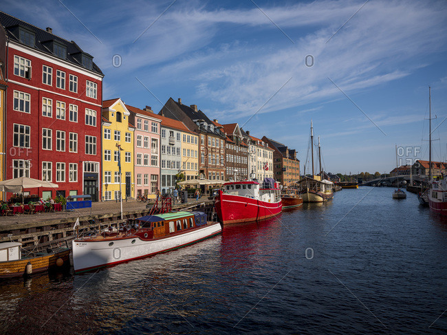 September 22, 2020: Denmark- Copenhagen- Boats moored along Nyhavn promenade with row of historical townhouses in background