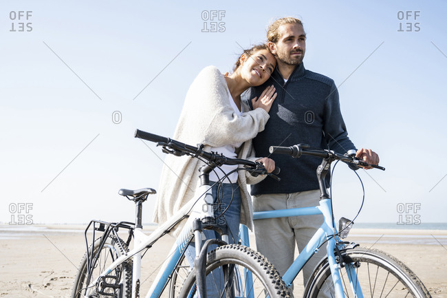 Smiling beautiful woman with head on boyfriend's shoulder standing with bicycles at beach against clear sky on sunny day