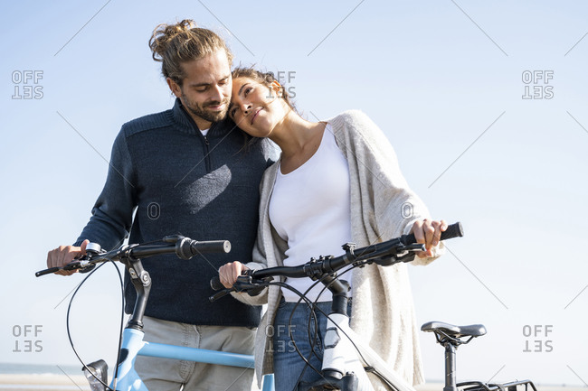 Beautiful woman with head on boyfriend's shoulder standing with bicycles at beach against clear sky on sunny day