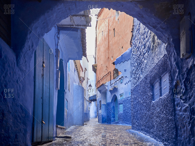 Morocco- Chefchaouen Province- Chefchaouen- Archway of empty cobblestone alley between old blue-colored houses