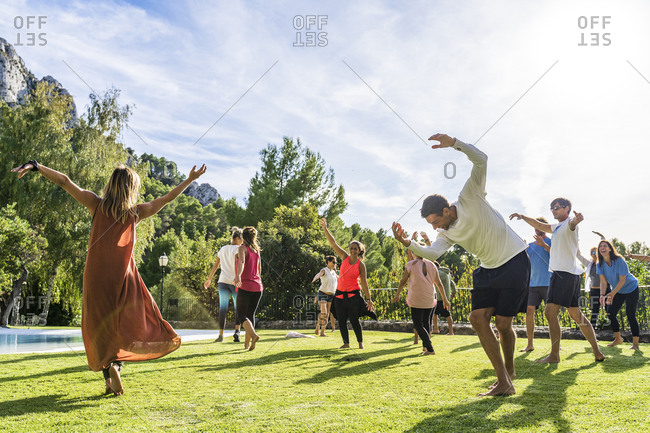 Mature female fitness instructor dancing with tourists at health retreat on grass against sky during sunny day