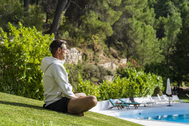 Male tourist meditating while practicing yoga on grass near swimming pool at health retreat during sunny day