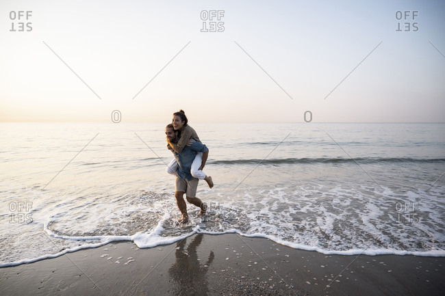 Cheerful man giving piggyback to girlfriend while walking on shore at beach against clear sky during sunset