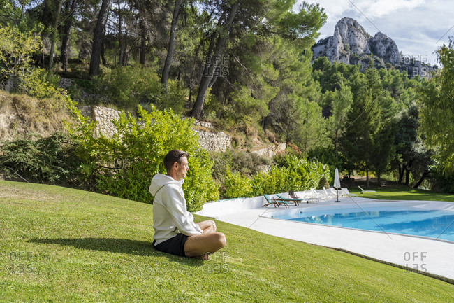 Mature man meditating while practicing yoga on grass near swimming pool at health retreat during sunny day