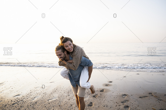 Happy man giving piggyback to girlfriend while walking on shore at beach against clear sky during sunset