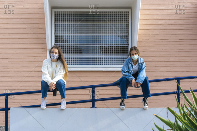 Teenage friends social distancing while wearing protective face mask sitting on railing during covid-19