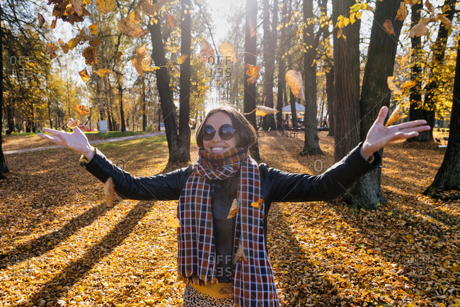 Smiling beautiful woman with arms outstretched throwing dry leaves while standing at park during autumn