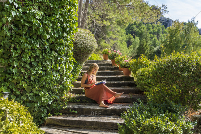Mature woman reading book while sitting on steps amidst green plants at health retreat during sunny day